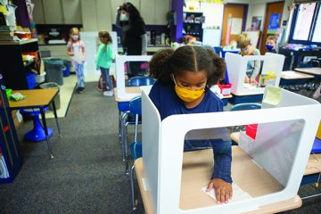 Elementary student cleaning desk